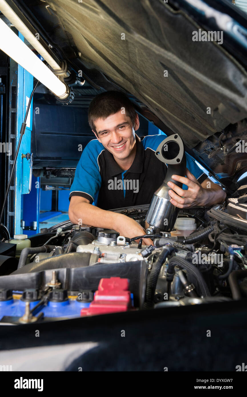 Apprentice mechanic under car hood - Stock Image