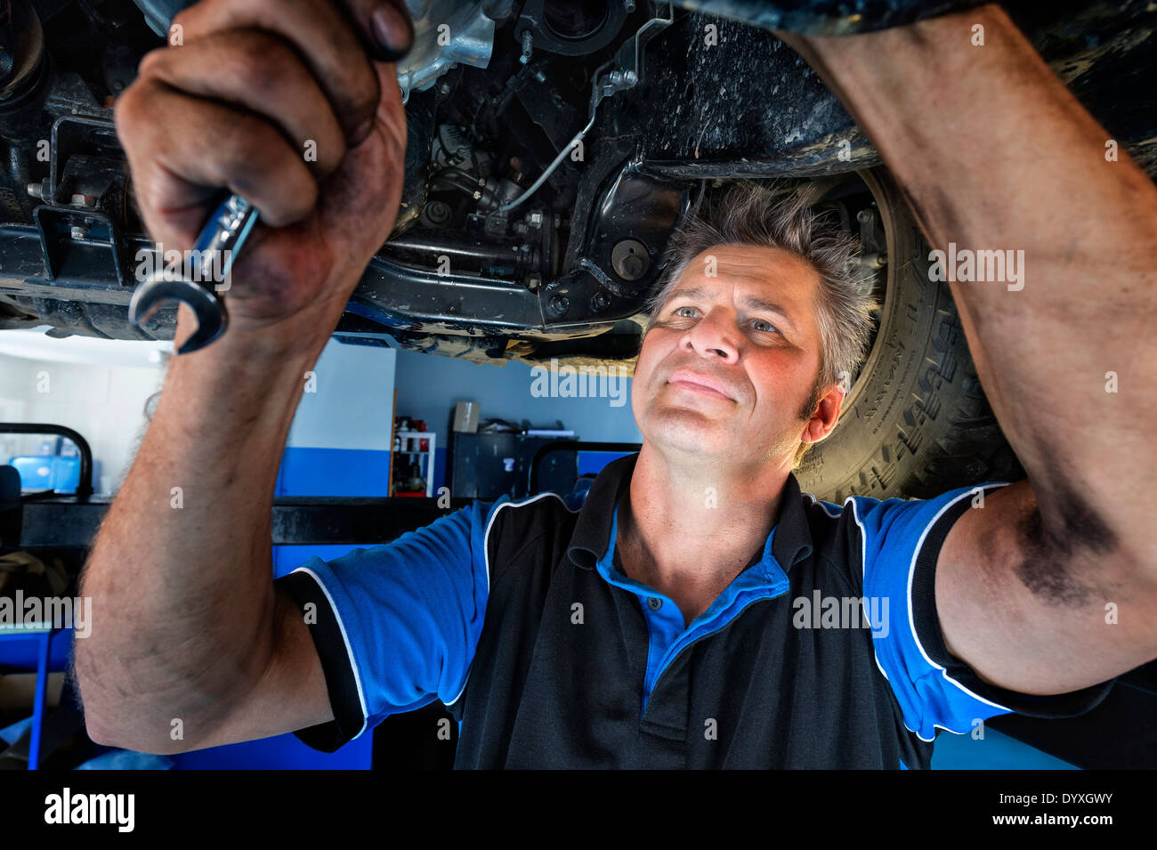 Mechanic working under car - Stock Image