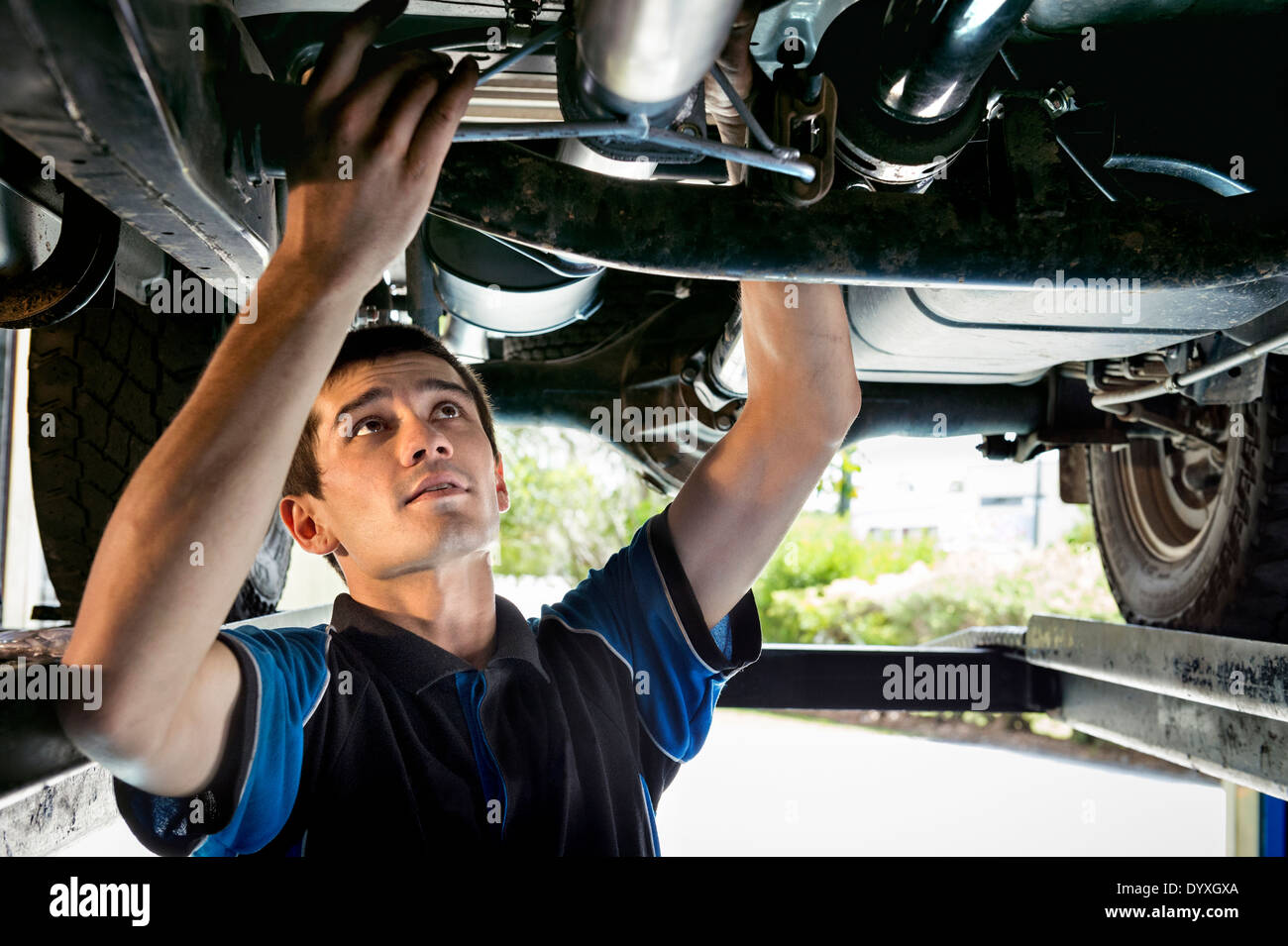 Young mechanic working under car - Stock Image