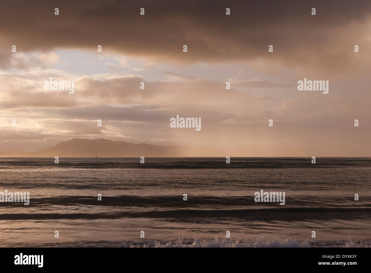 low wide view across ocean with gentle waves at sunset with back lit rain falling on ocean and distant mountains. - Stock Image