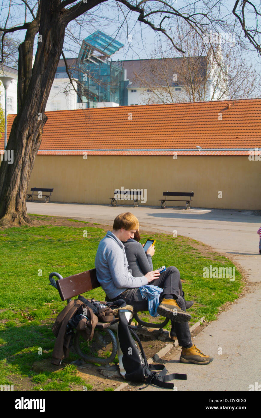 Young couple in their 20s both reading ebooks, Kampa island, Mala strana, Prague, Czech Republic, Europe - Stock Image