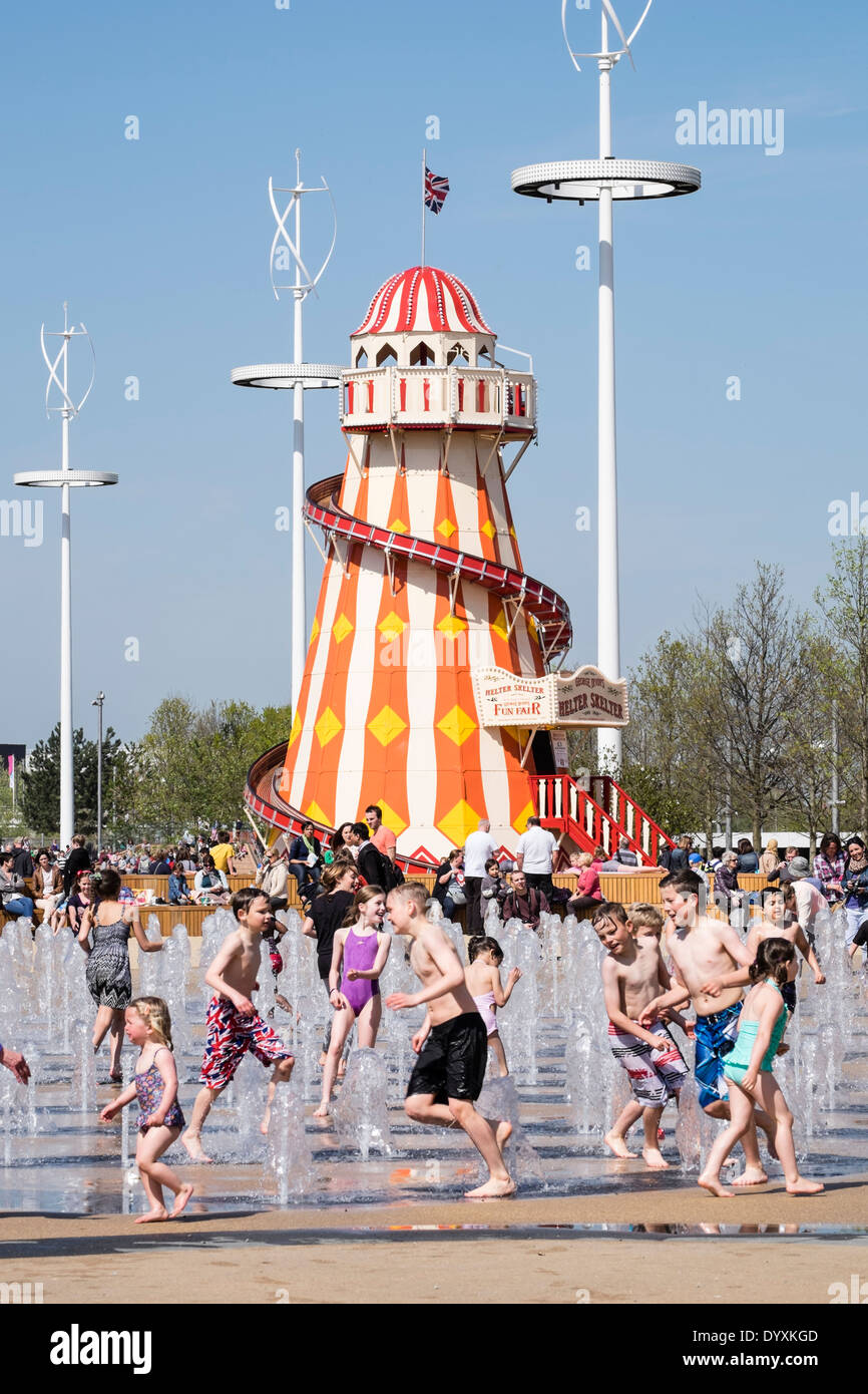 Helter Skelter funfair and fountain with many visitors at Queen Elizabeth Olympic Park in Stratford London United Kingdom - Stock Image