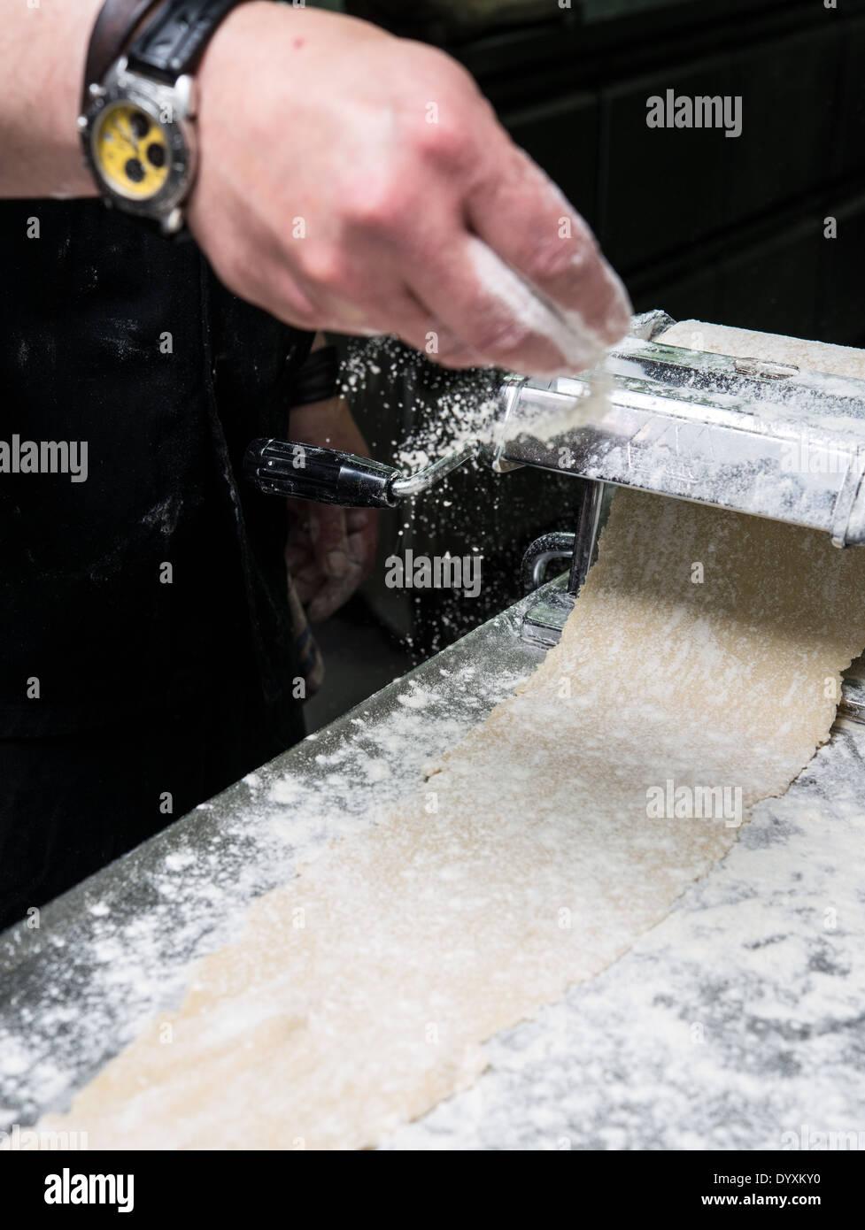 Making Tortellini pasta flattening the dough - Stock Image