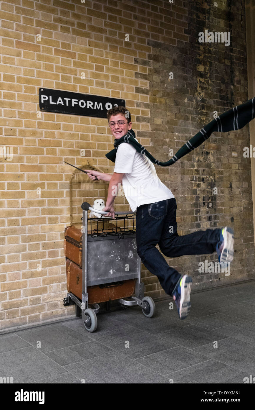 Harry Potter fan jumping at Platform 9 3/4 at King's Cross Station in London United Kingdom - Stock Image