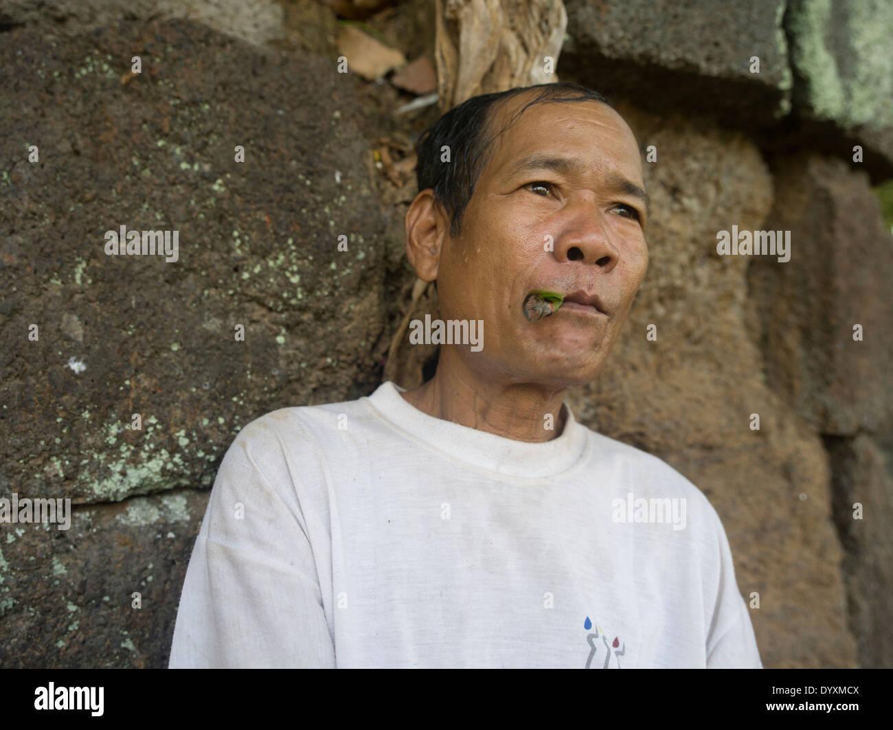 Camobdian man smoking a leaf cigar at Prasat Thom the principal monument of Koh Ker 127 NE of Siem Reap, Cambodia - Stock Image