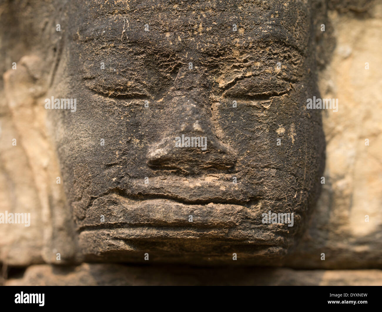 Stone carving of a face beside the Terrace of Elephants, Angkor Thom Temple, Siem Reap, Cambodia - Stock Image