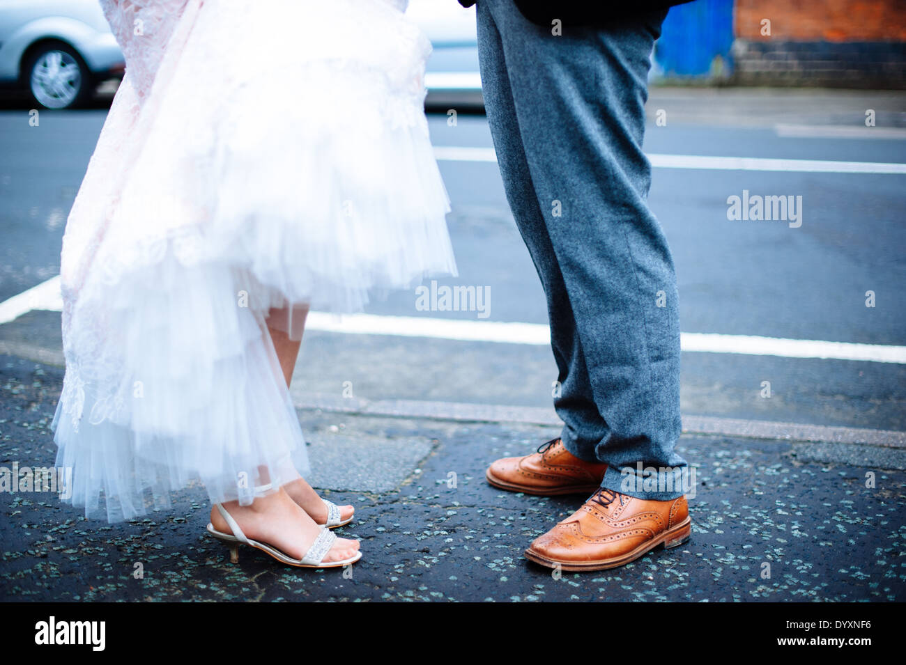 Legs And Shoes Of A Bride And Groom Standing Facing Each Other On
