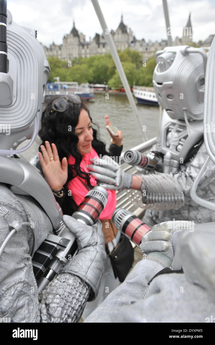 Embankment, London, UK. 27th April 2014. A tourist is attacked by Cybermen in the costume parade for the Sci-Fi London Festival which heads towards the BFI. Credit:  Matthew Chattle/Alamy Live News - Stock Image
