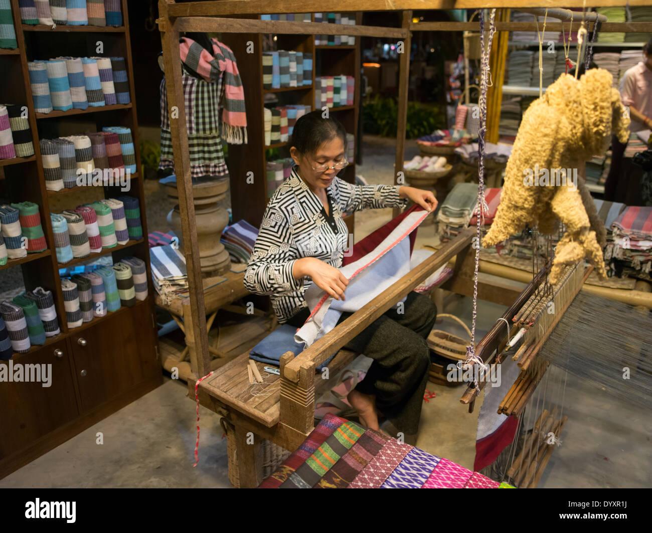 Woman weaving cloth in Angkor Night Market, Siem Reap, Cambodia - Stock Image