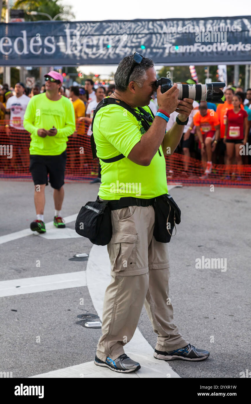Professional photographer working the starting line of the 2014 Mercedes-Benz Corporate Run in Miami, Florida, USA. Stock Photo
