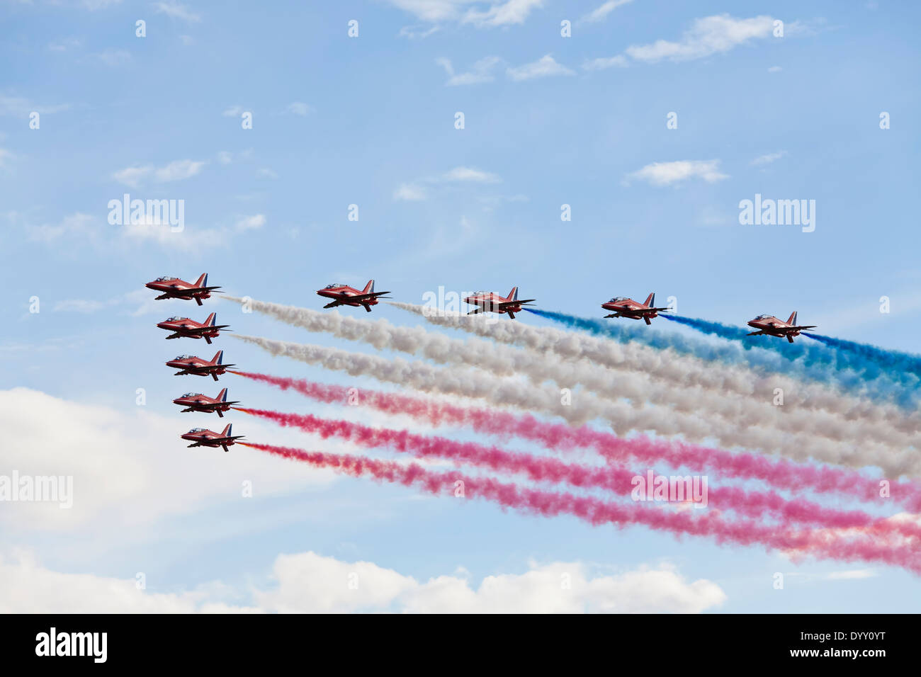 Red Arrows performing a slow flypast with red white and blue smoke. - Stock Image