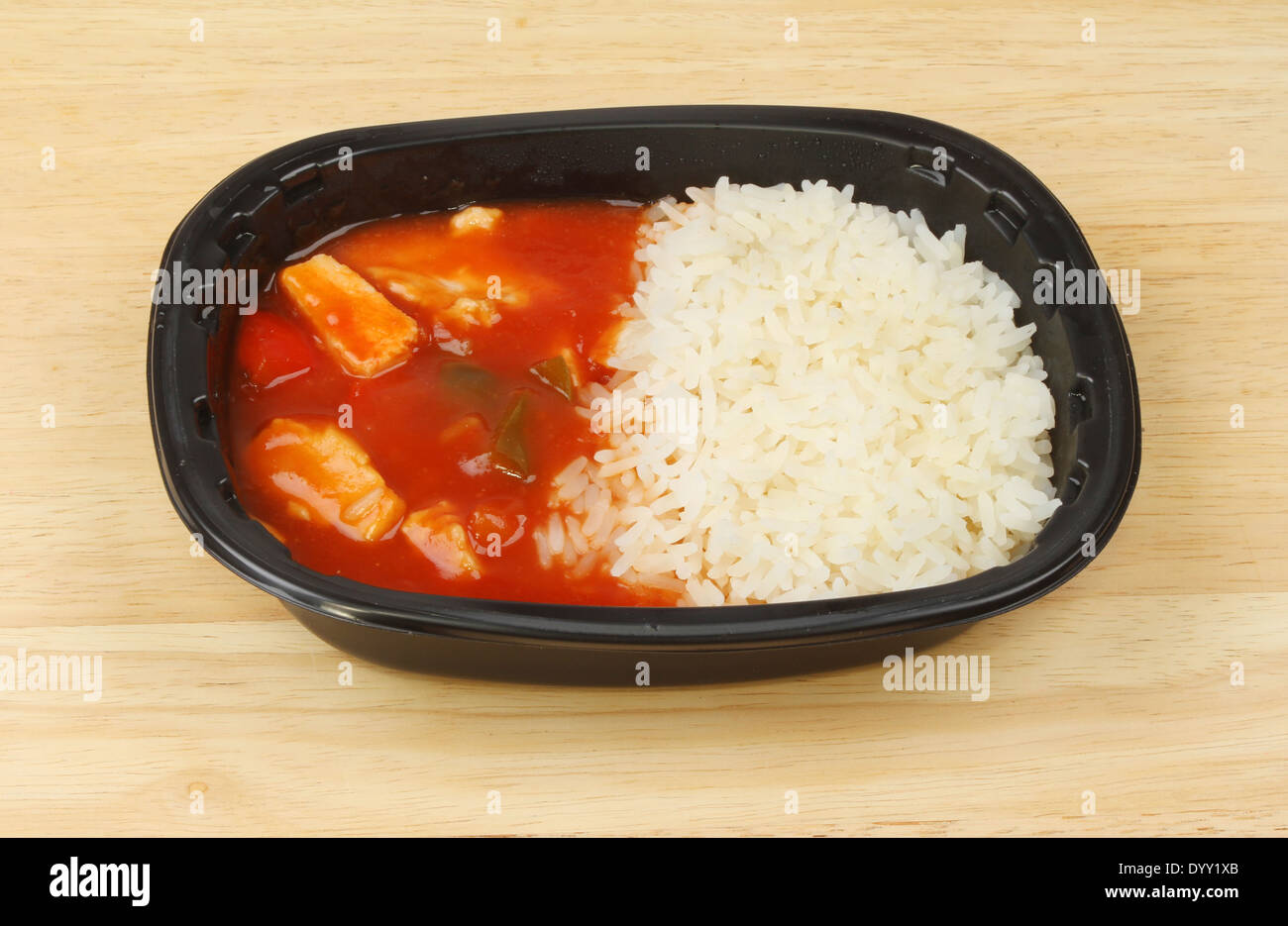 Convenience meal of Chinese sweet and sour chicken in a plastic carton on a wooden worktop - Stock Image