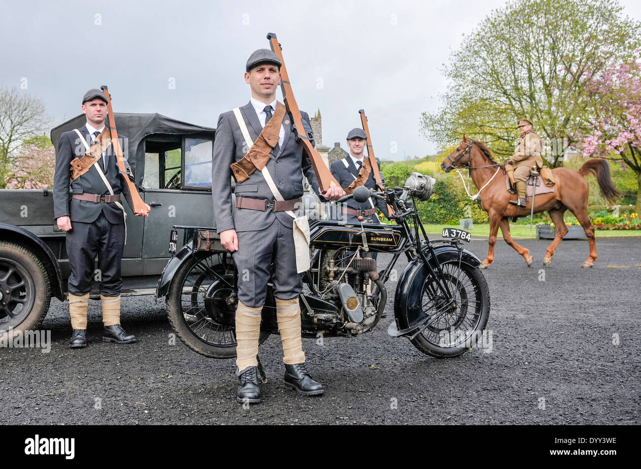 Three men dressed as members of the Ulster Volunteer Force (UVF) carry wooden rifles, as a solder rides past on Stock Photo