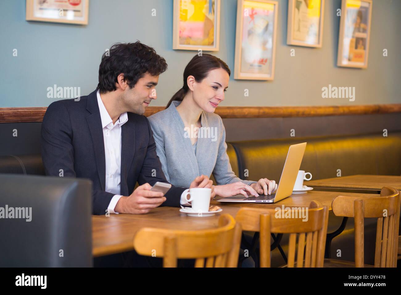 Business woman man computer colleague restaurant - Stock Image