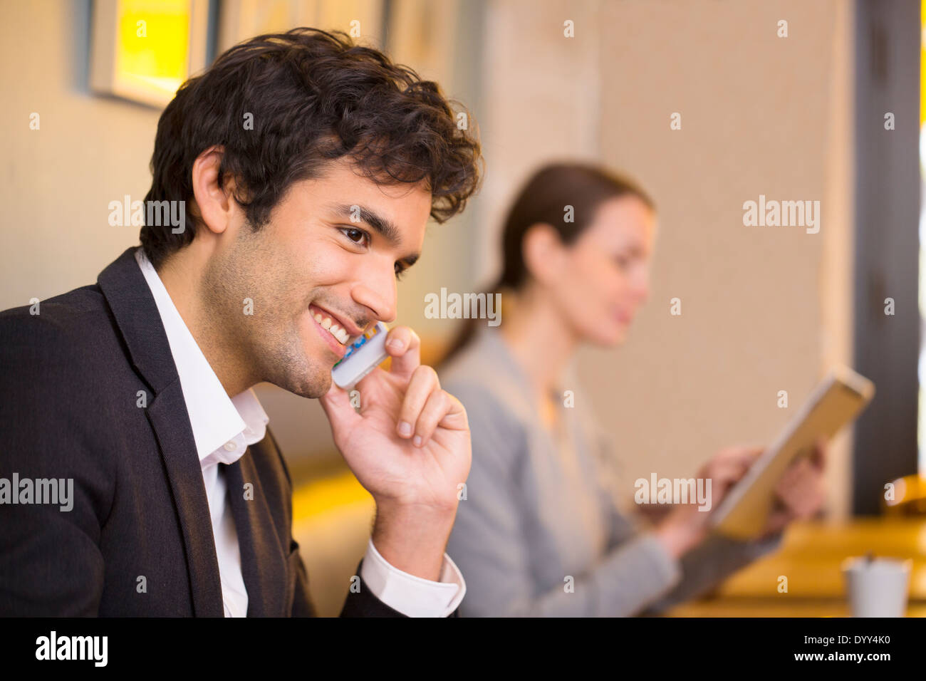 male cheerful calling restaurant smartphone cafe female tablet pc - Stock Image