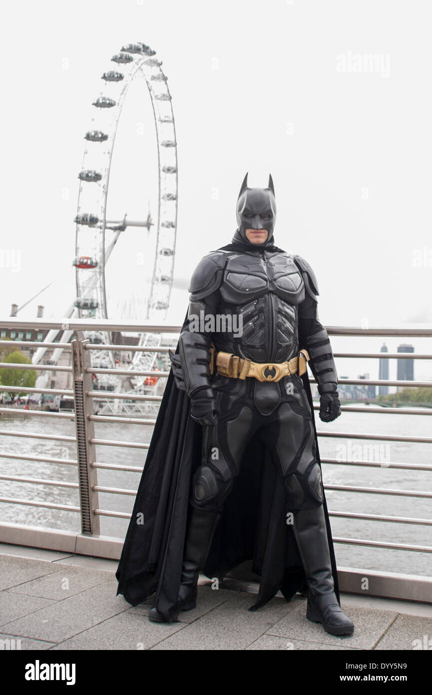 London, 27 April 2014 - people dressed as their favourite sci-fi characters take part in the Sci-Fi London 2014 costume parade starting at Somerset House and finishing at the BFI on the South Bank.  Batman on Hungerford Bridge, with the London Eye in the distance.    Credit:  Stephen Chung/Alamy Live News - Stock Image
