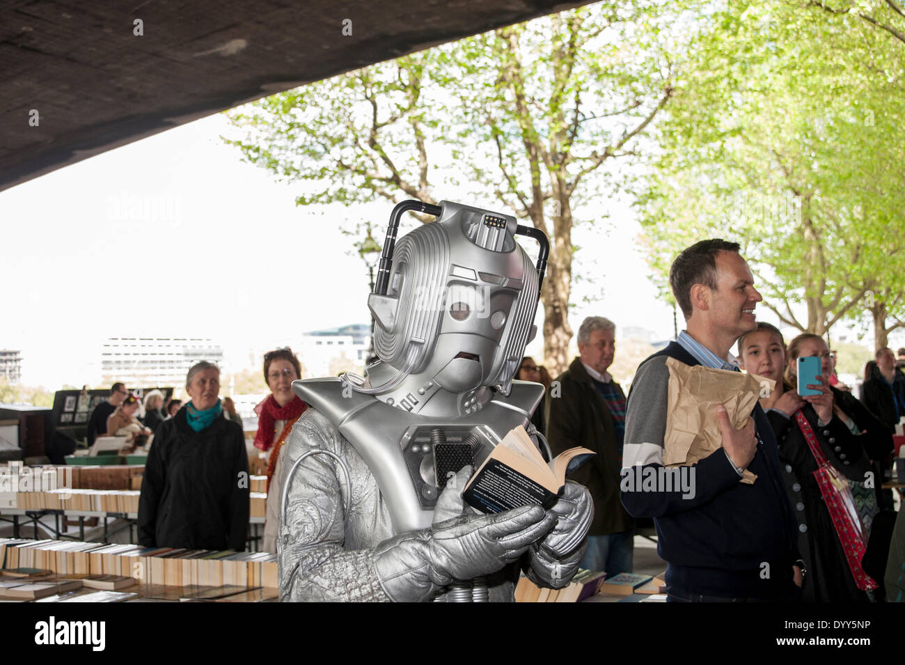 London, 27 April 2014 - people dressed as their favourite sci-fi characters take part in the Sci-Fi London 2014 costume parade starting at Somerset House and finishing at the BFI on the South Bank.  A cyberman reads a book at the book market underneath Waterloo Bridge.    Credit:  Stephen Chung/Alamy Live News - Stock Image