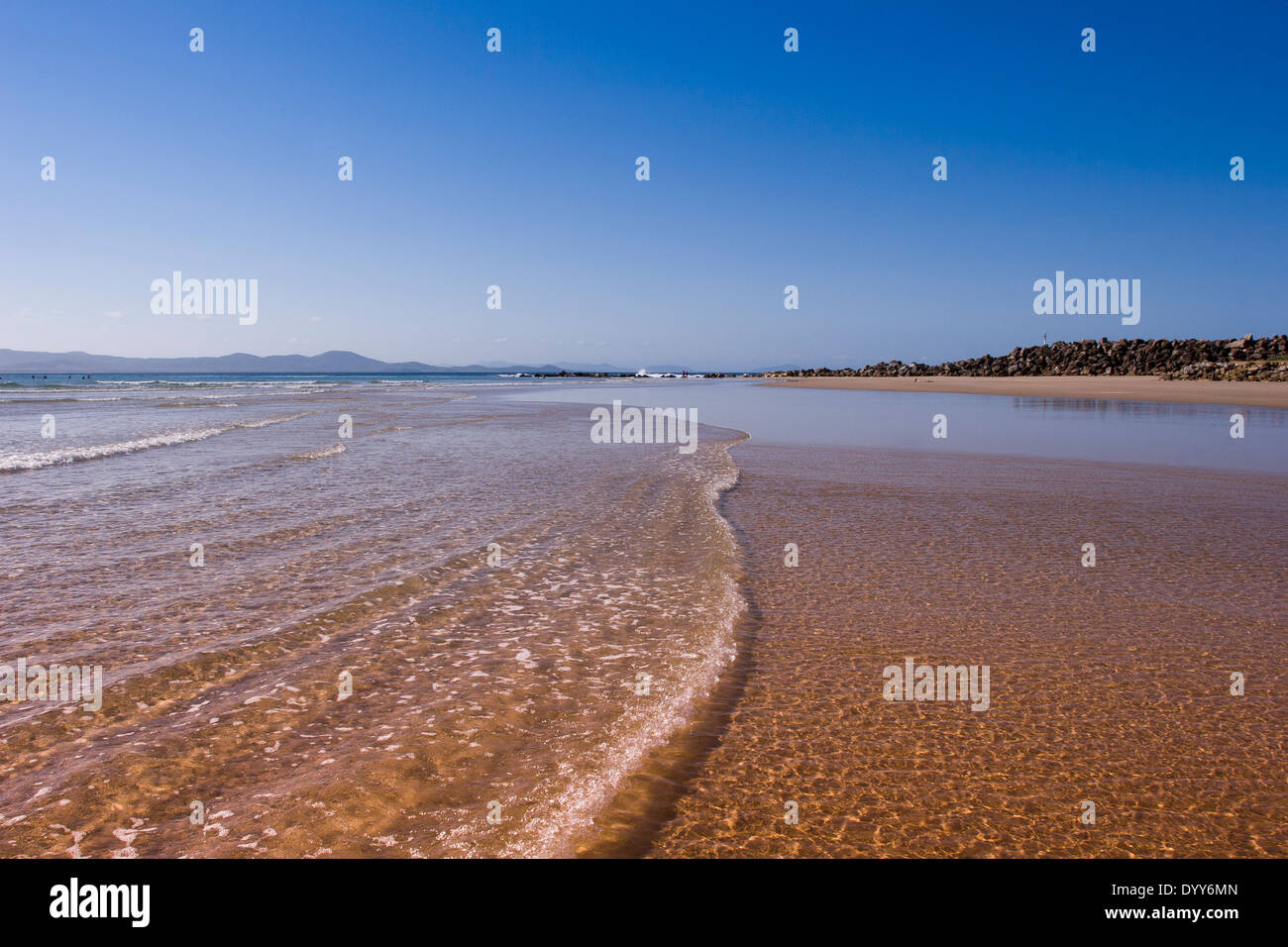low angle view across tidal flats at the beach edge with gentle wave, distant hills, and ocean rock pier on sunny blue sky day - Stock Image