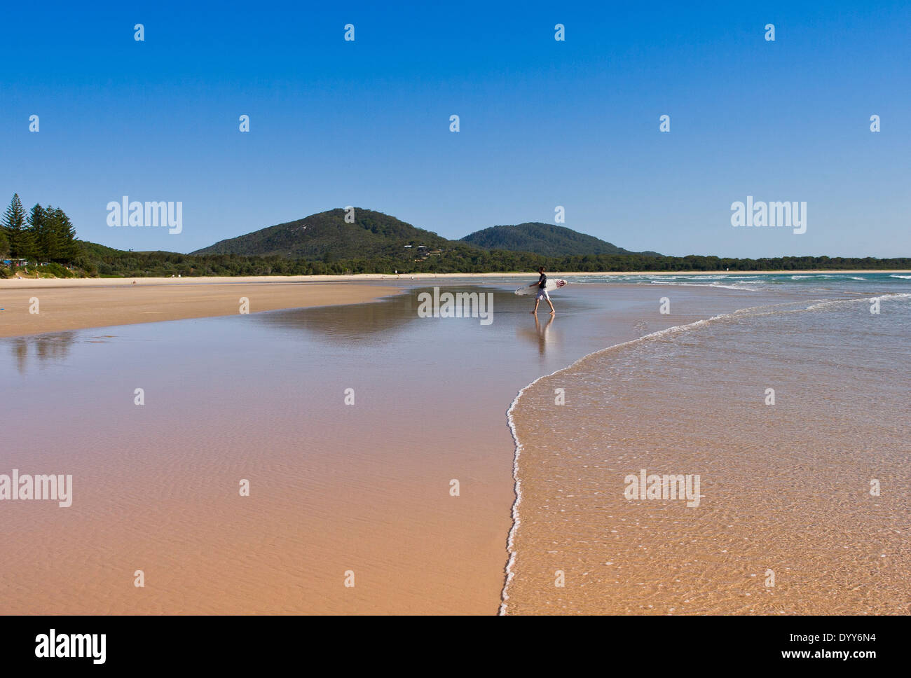 low angle view across tidal flats at the beach edge with gentle wave, surfer walking on beach, and distant hills, on sunny day - Stock Image
