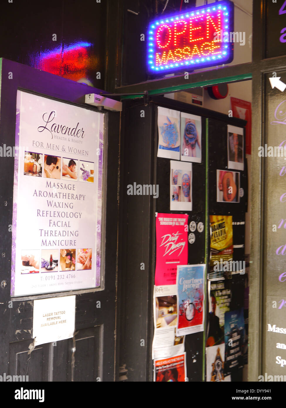 Massage parlour doorway with neon sign and bill posters / advertisments - Stock Image