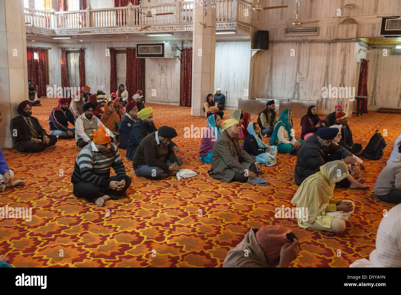 New Delhi, India. Worshipers inside a Sikh Temple (Bangla Sahib Gurudwara) waiting for a Prayer Service to Begin. - Stock Image