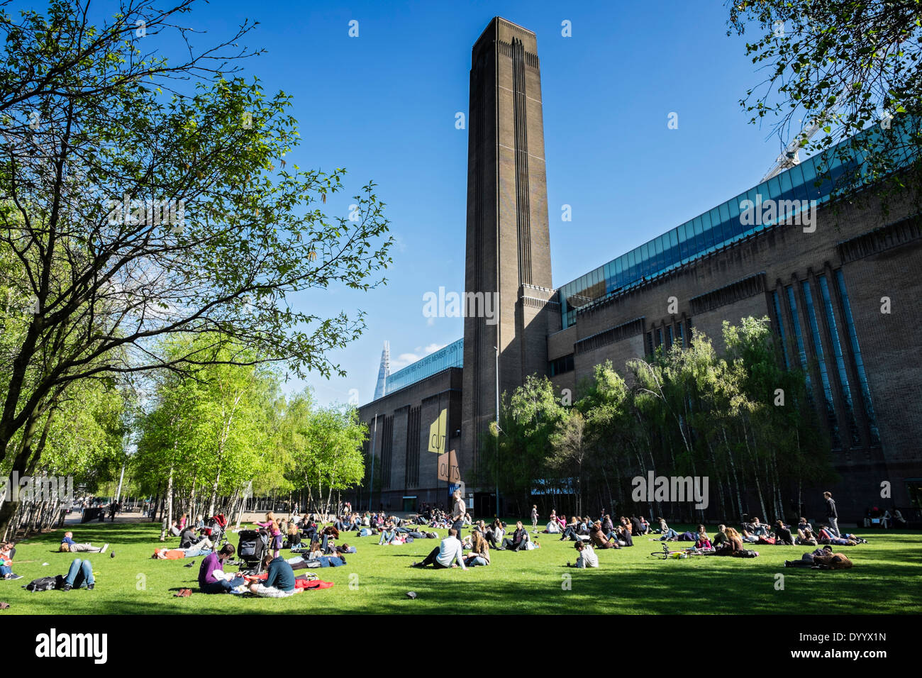People relaxing in park in front of Tate Modern art gallery in London United Kingdom - Stock Image