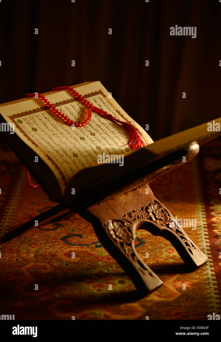 Holy Quran and rosary beads on a wooden stand - Stock Image