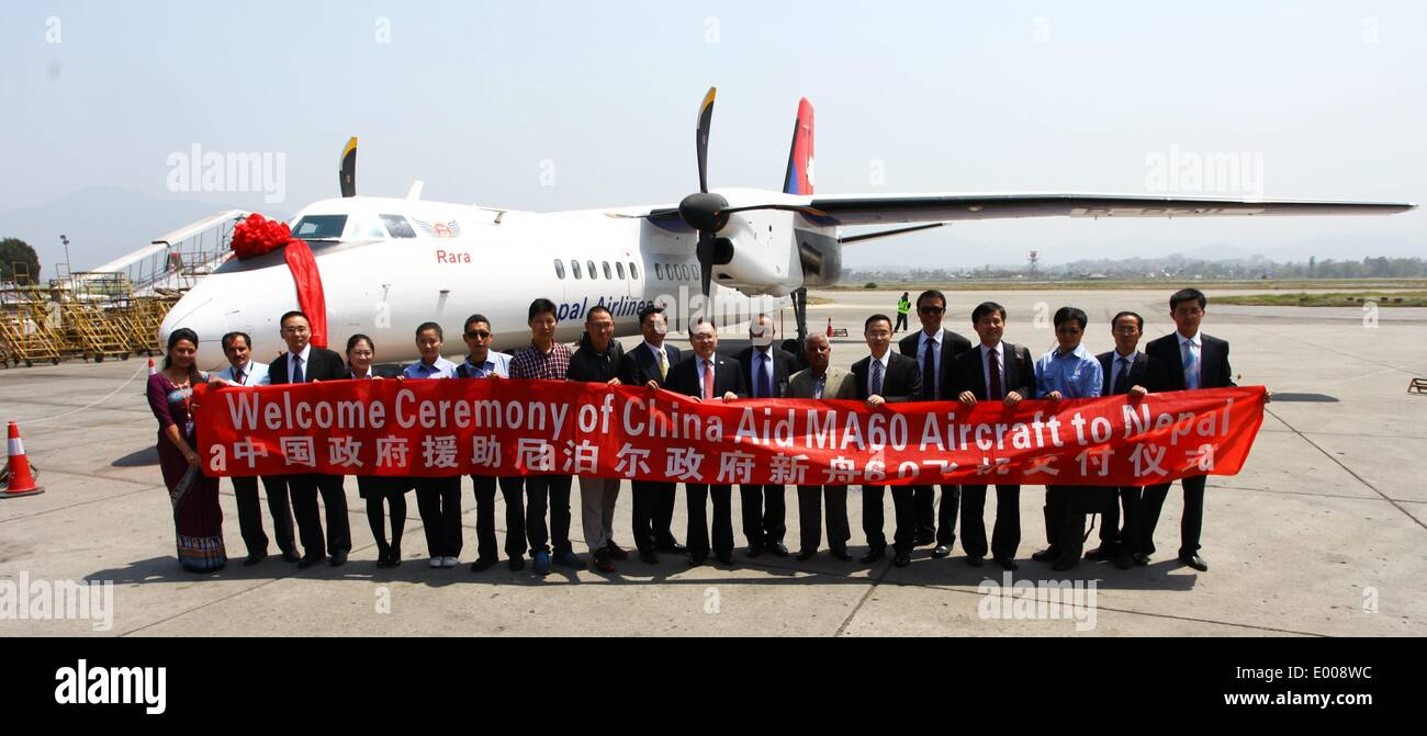 Kathmandu, Nepal. 28th Apr, 2014. Staff members of Chinese Aviation and Nepal Airlines pose for a photograph during the handing over ceremony of the China-made air carrier Modern Ark 60 (MA60) at Tribhuvan International Airport in Kathmandu, Nepal, April 28, 2014. The long wait of Nepal government to receive the first China-made air carrier has finally been over Sunday afternoon with the landing of a 58-seater Modern Ark 60 (MA60) at the country's only international airport. © Sunil Sharma/Xinhua/Alamy Live News - Stock Image