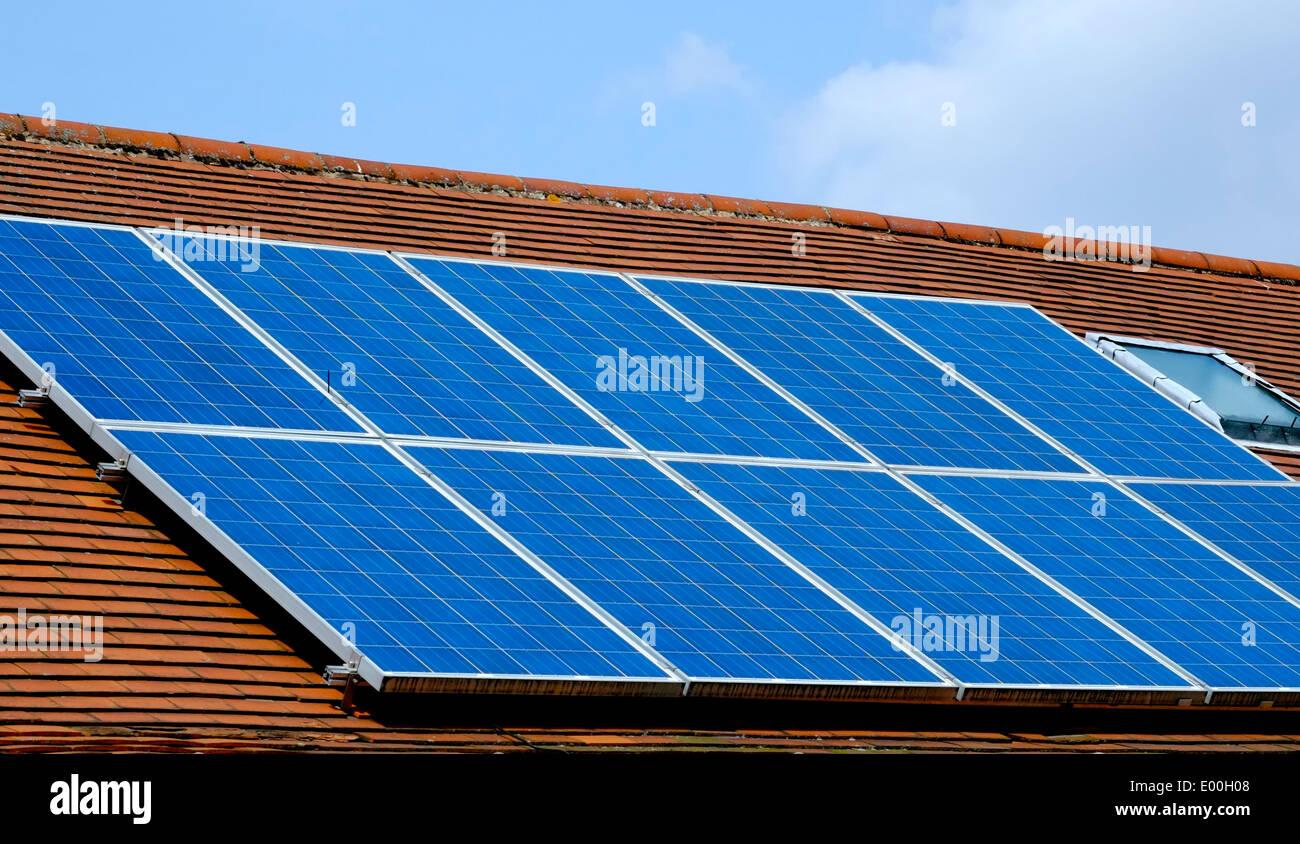 Solar energy panels on a slanting roof England UK - Stock Image