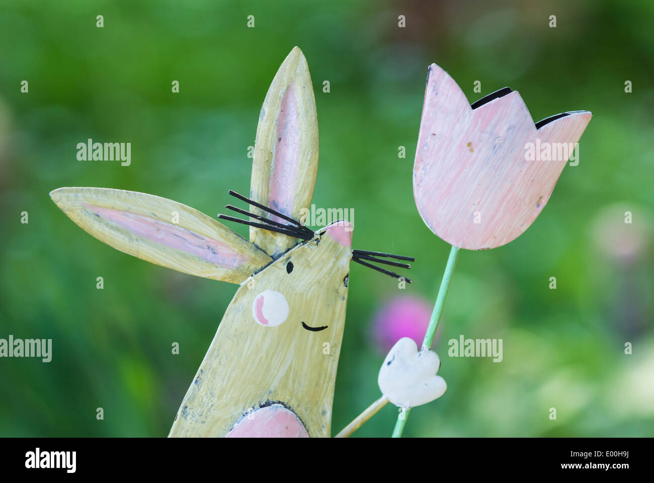 painted metal toy bunny against green garden background - Stock Image