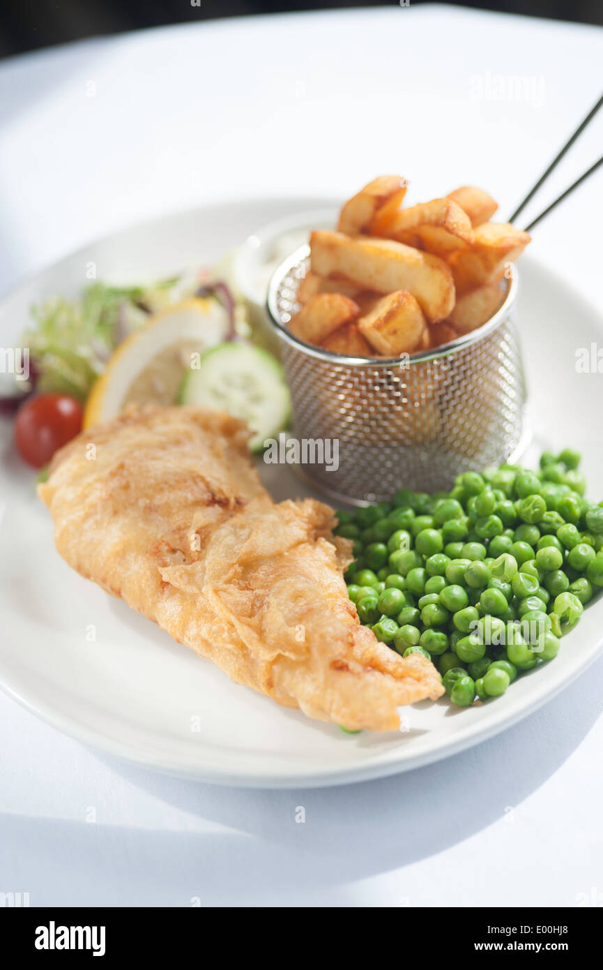 Fish and chips on a plate with peas. - Stock Image