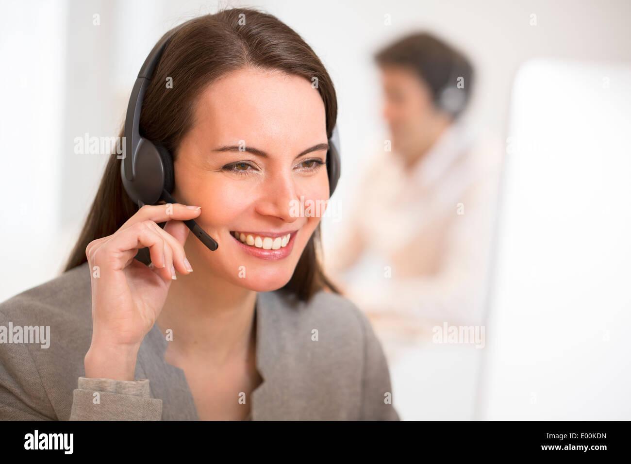 smiling Female pretty desk headphone portrait - Stock Image