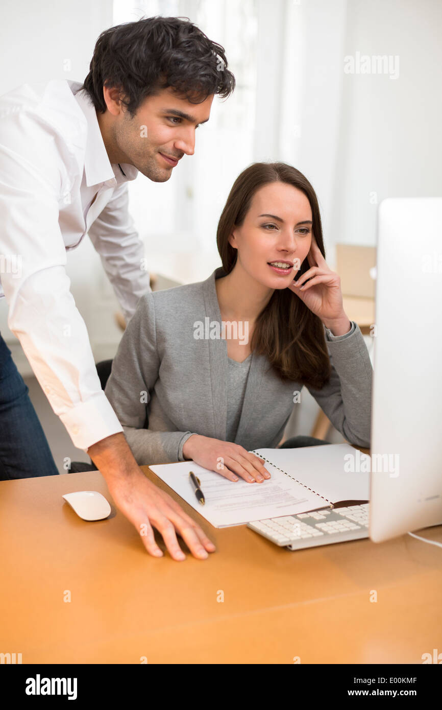 Male female business desk pc meeting - Stock Image