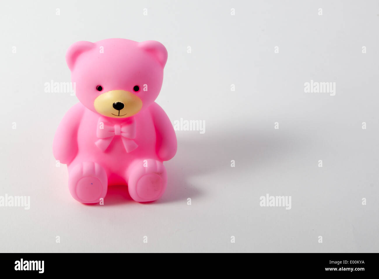 toys on a white background a pink teddy bear for a baby girl stock