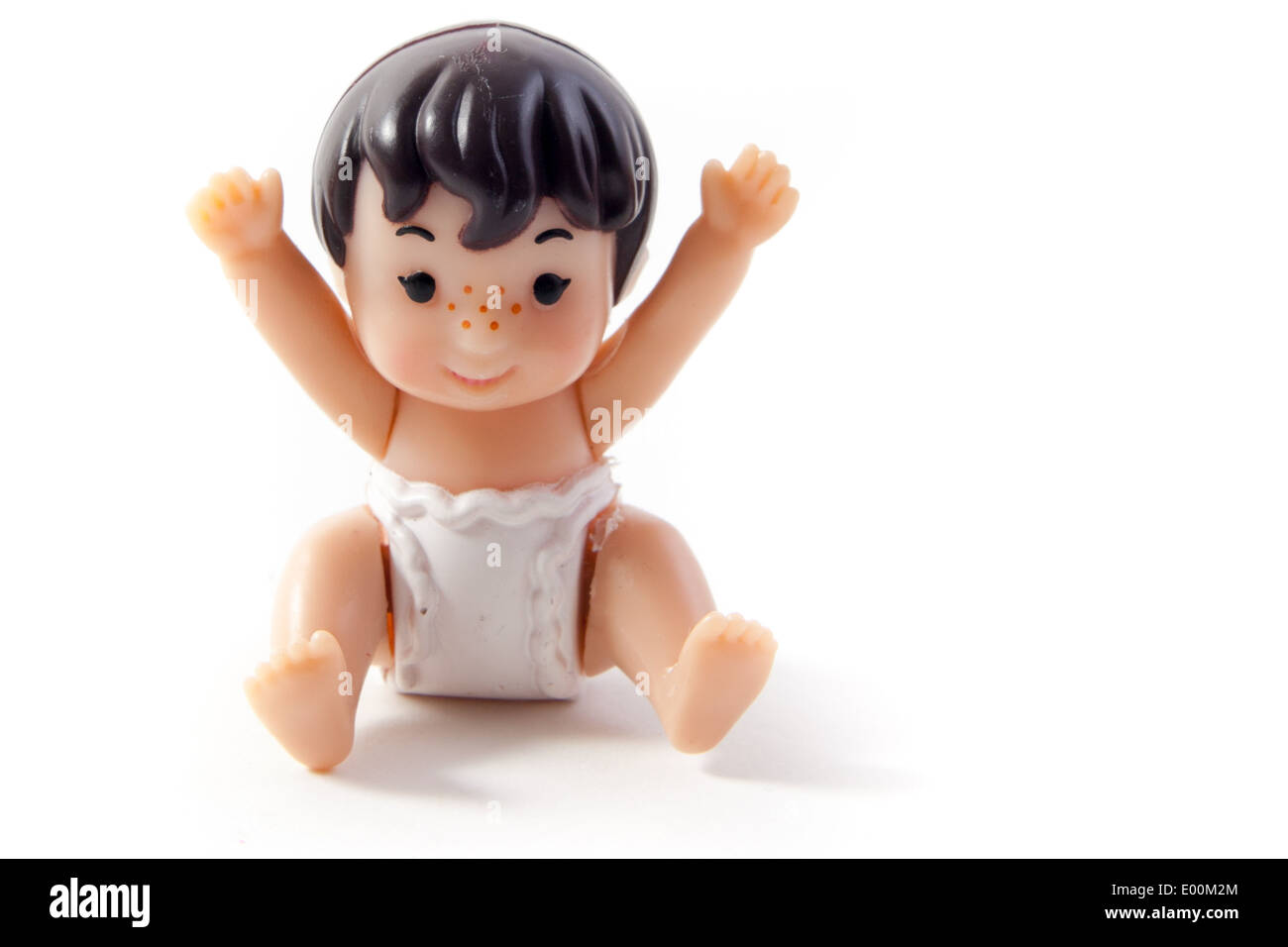 Toys on a white background. A plastic baby girl doll with nappy on holding her hands up. - Stock Image