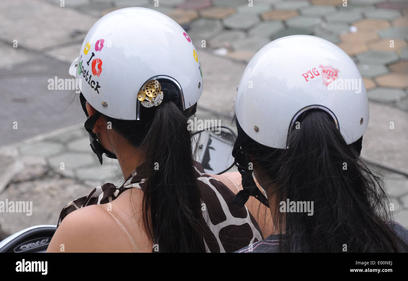 Two Vietnamese girls on a motorbike with helmets designed for pony tails - Stock Image