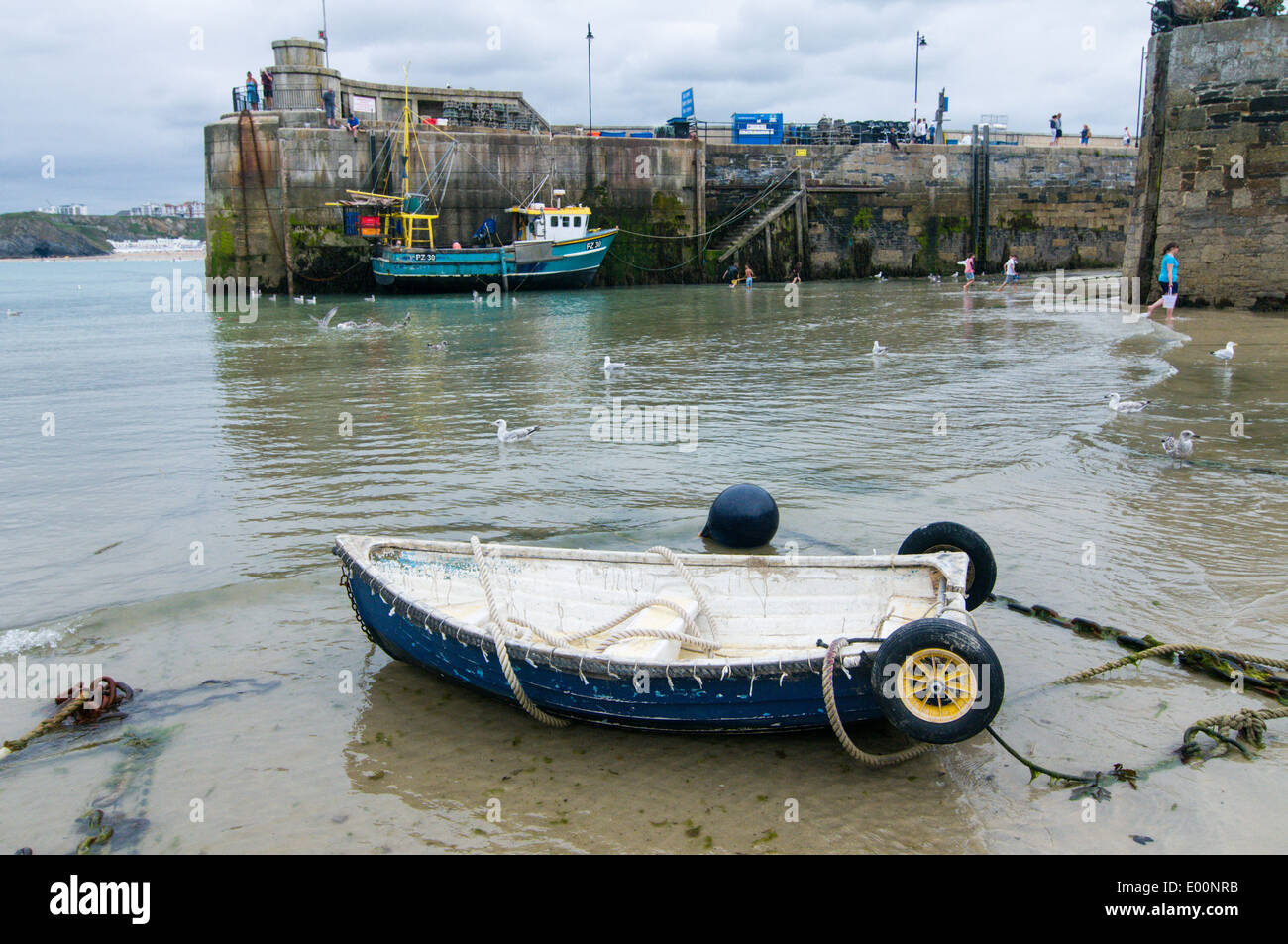 Small rowing boat and a fishing boat moored inside Newquay harbour. - Stock Image
