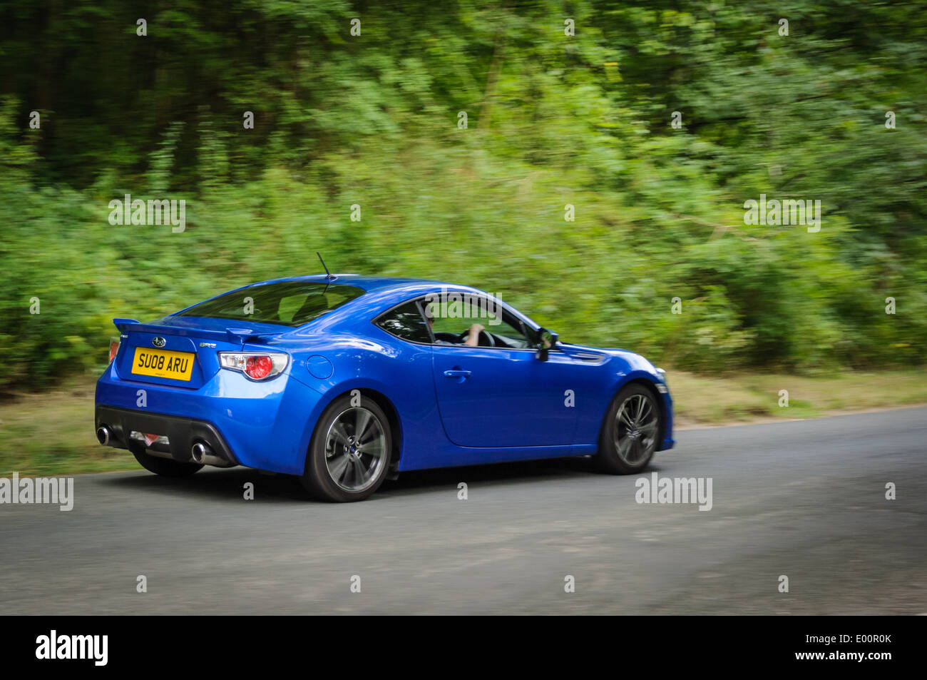 Driving a Subaru BRZ rear wheel drive sports car on an English country road - Stock Image