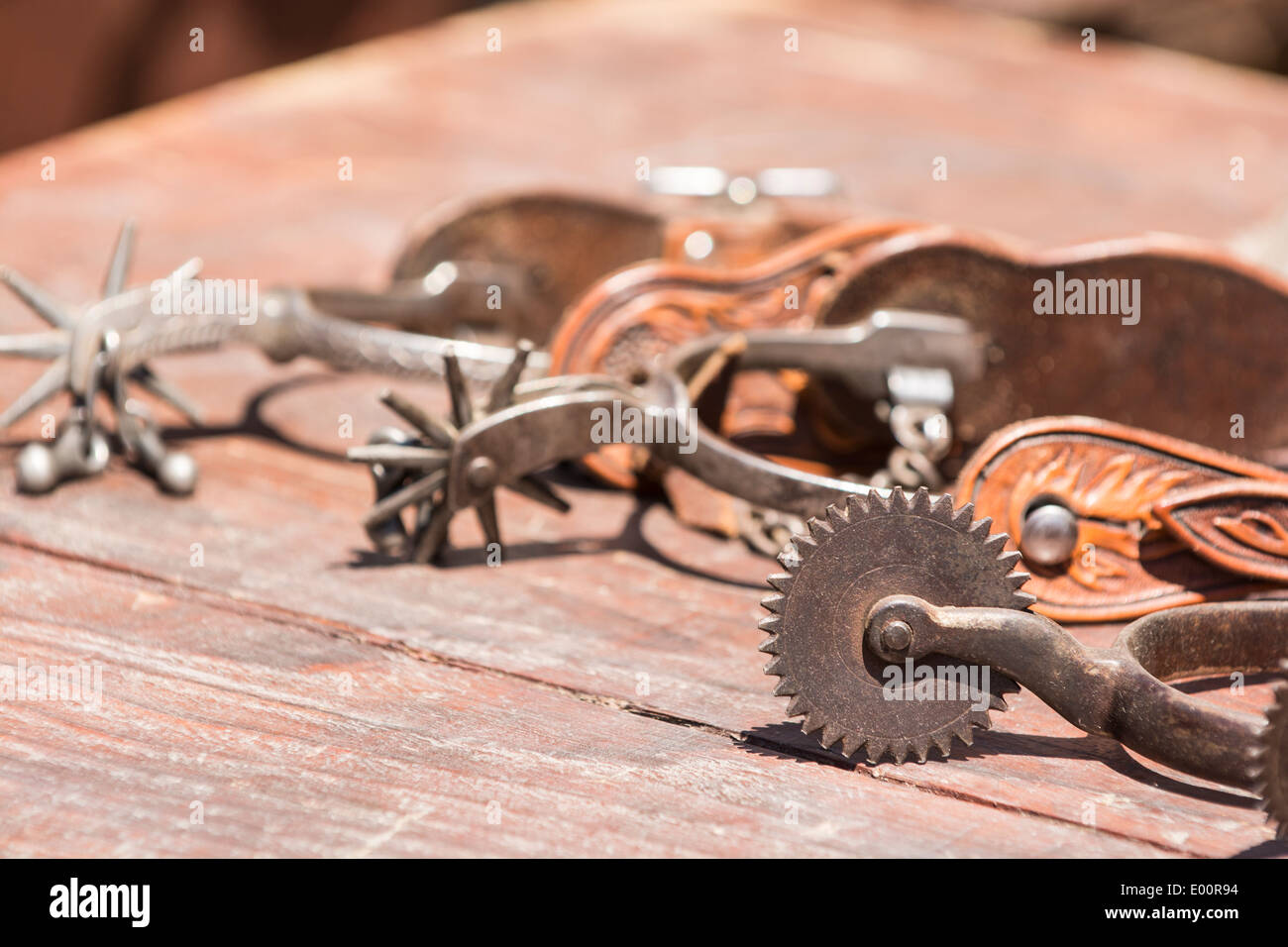 Three western boot spurs laying on a table - Stock Image