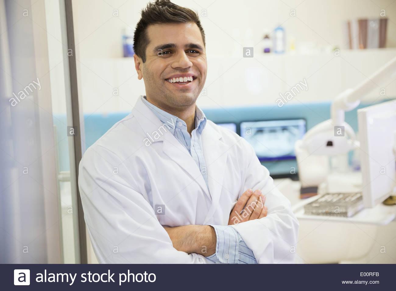 Dentist laughing in doorway of office - Stock Image