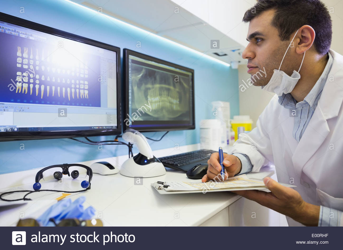 Dentist with clipboard examining tooth x-rays - Stock Image
