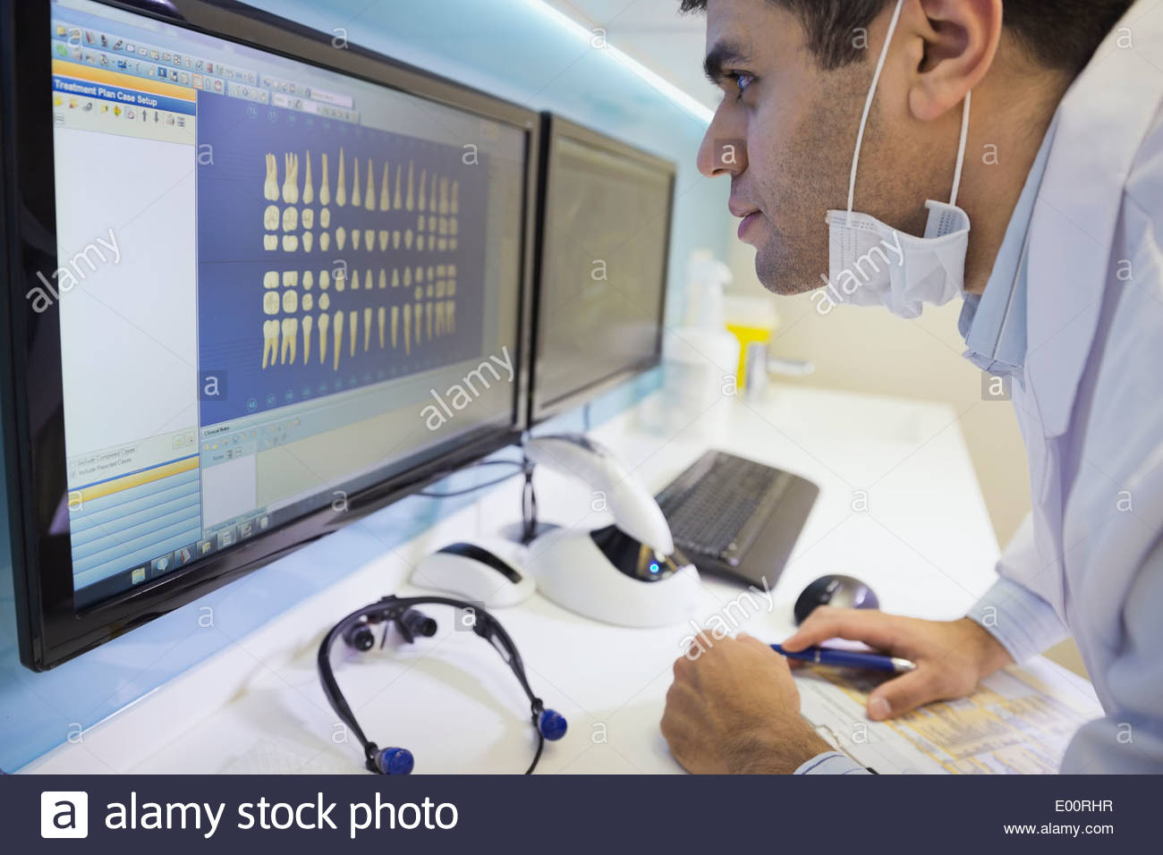 Dentist leaning in to examine tooth x-rays - Stock Image