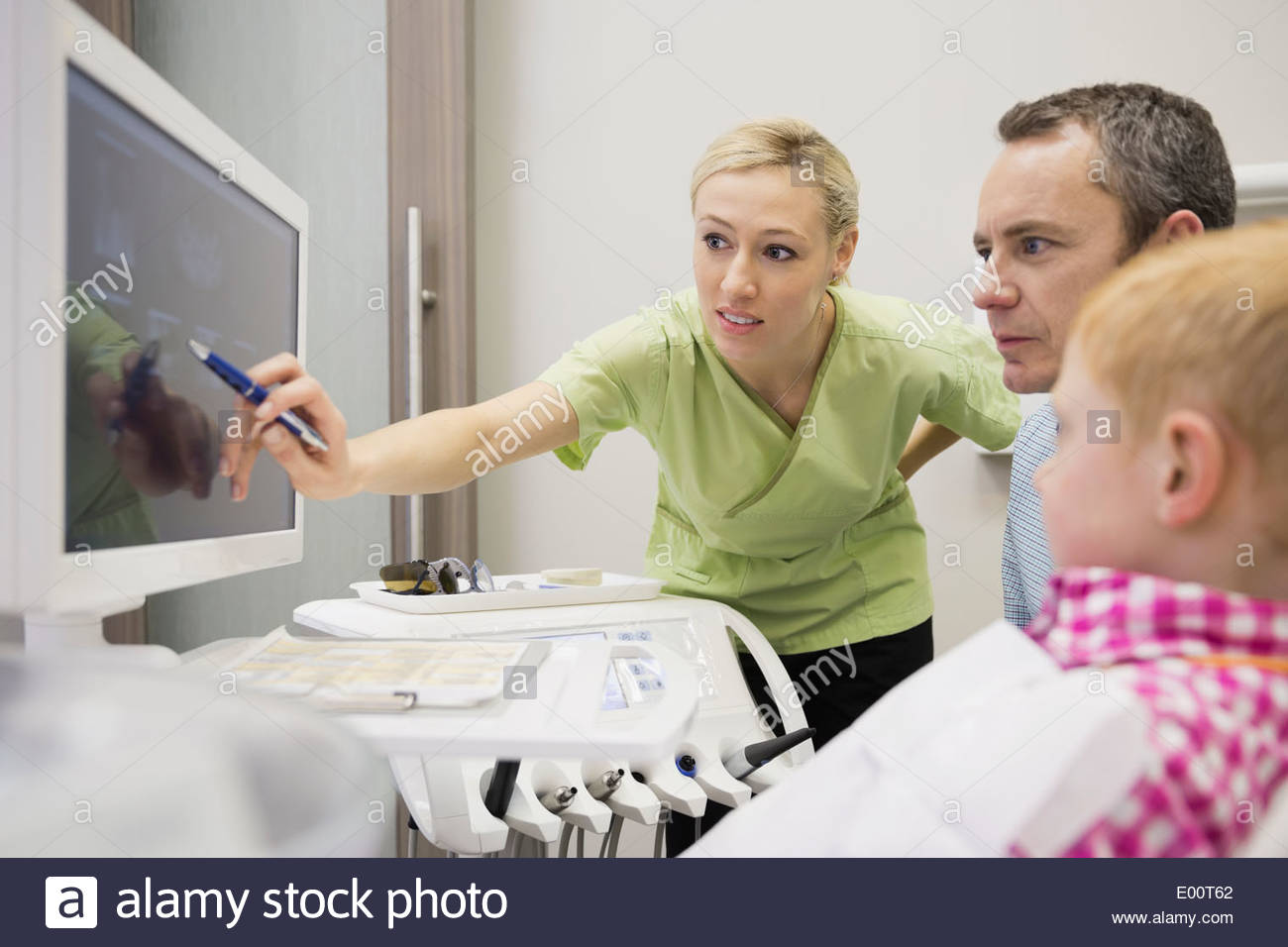 Dental assistant reviewing x-rays with patient - Stock Image