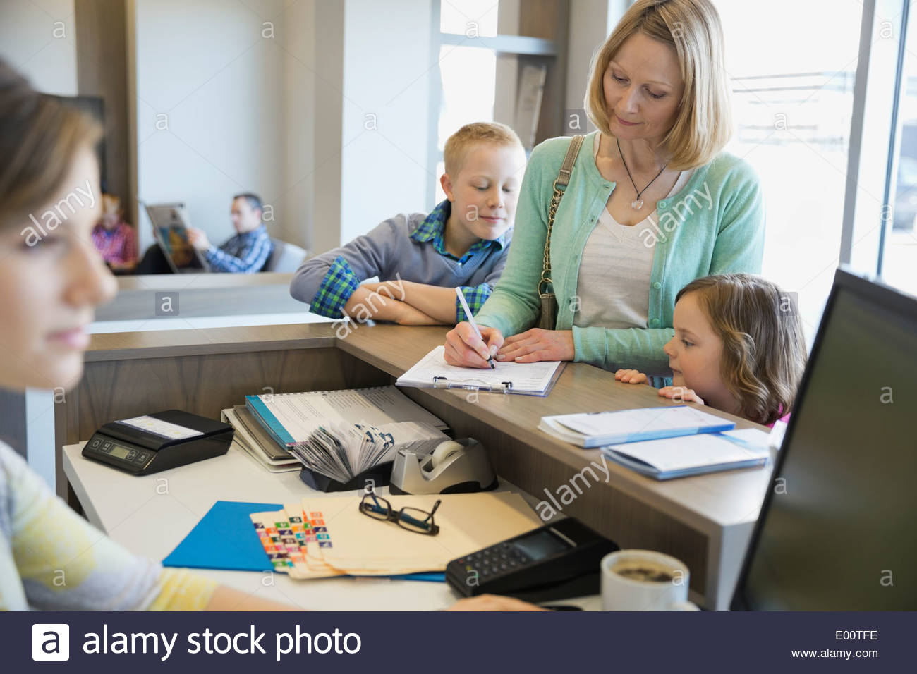 Woman filling out paperwork at dentists office - Stock Image