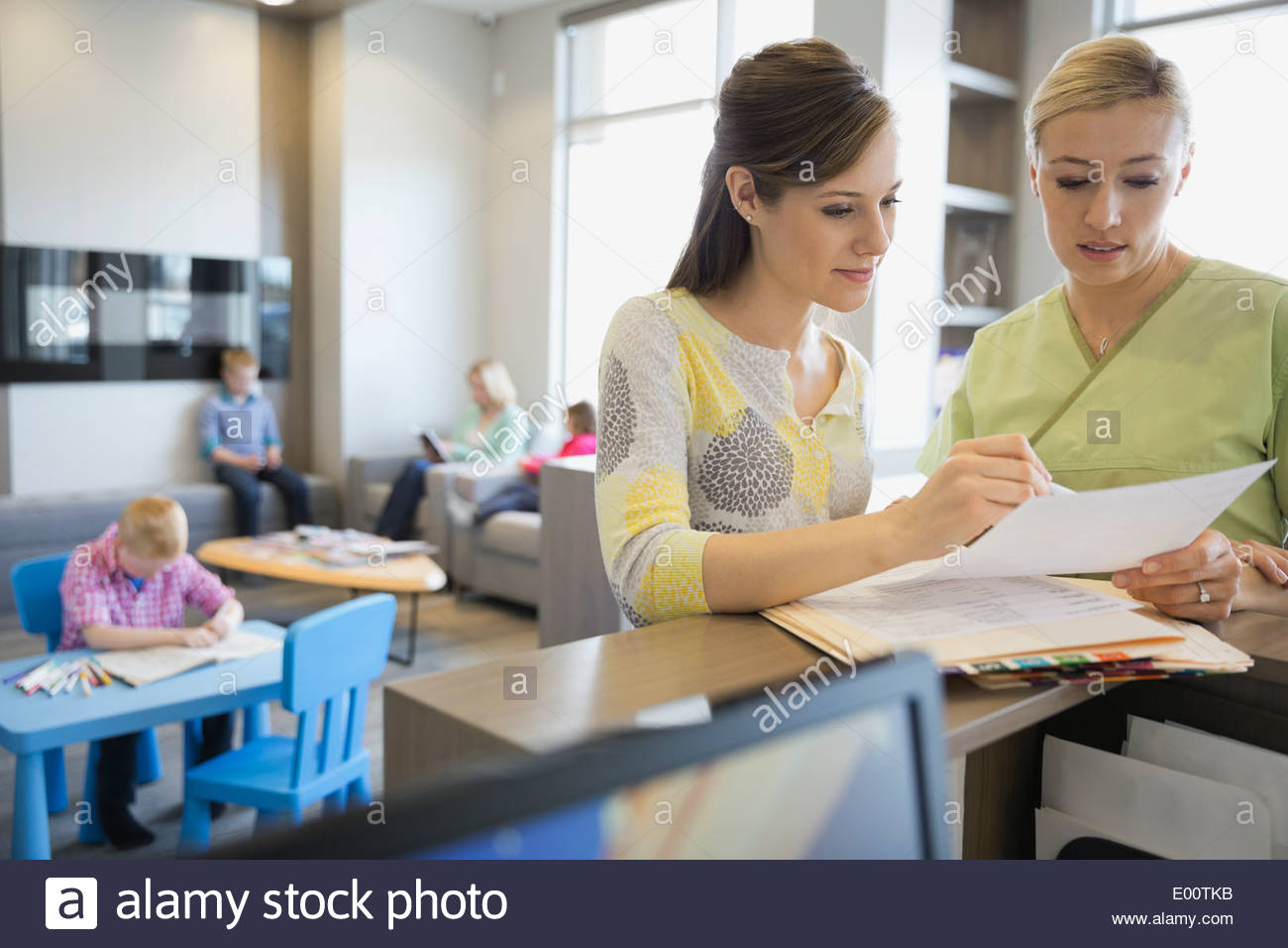 Elegant Dental Assistant And Receptionist Reviewing Medical Records   Stock Image