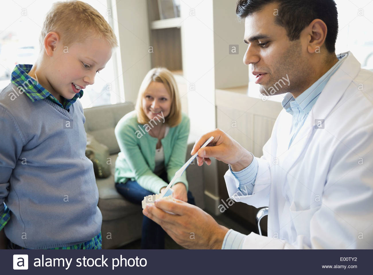Dentist showing boy how to brush teeth - Stock Image