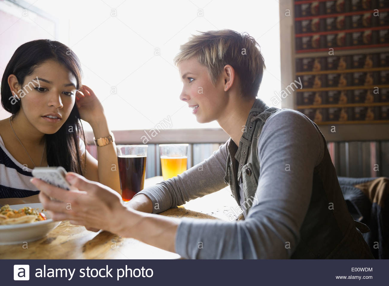 Women text messaging with cell phone at brewery - Stock Image