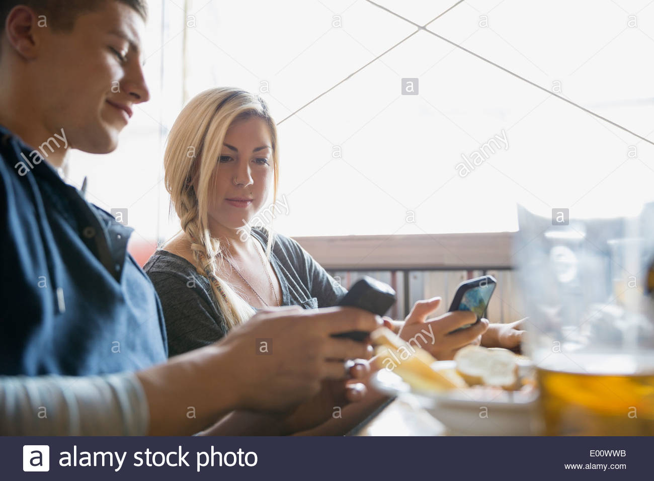 Couple text messaging with cell phones at brewery - Stock Image