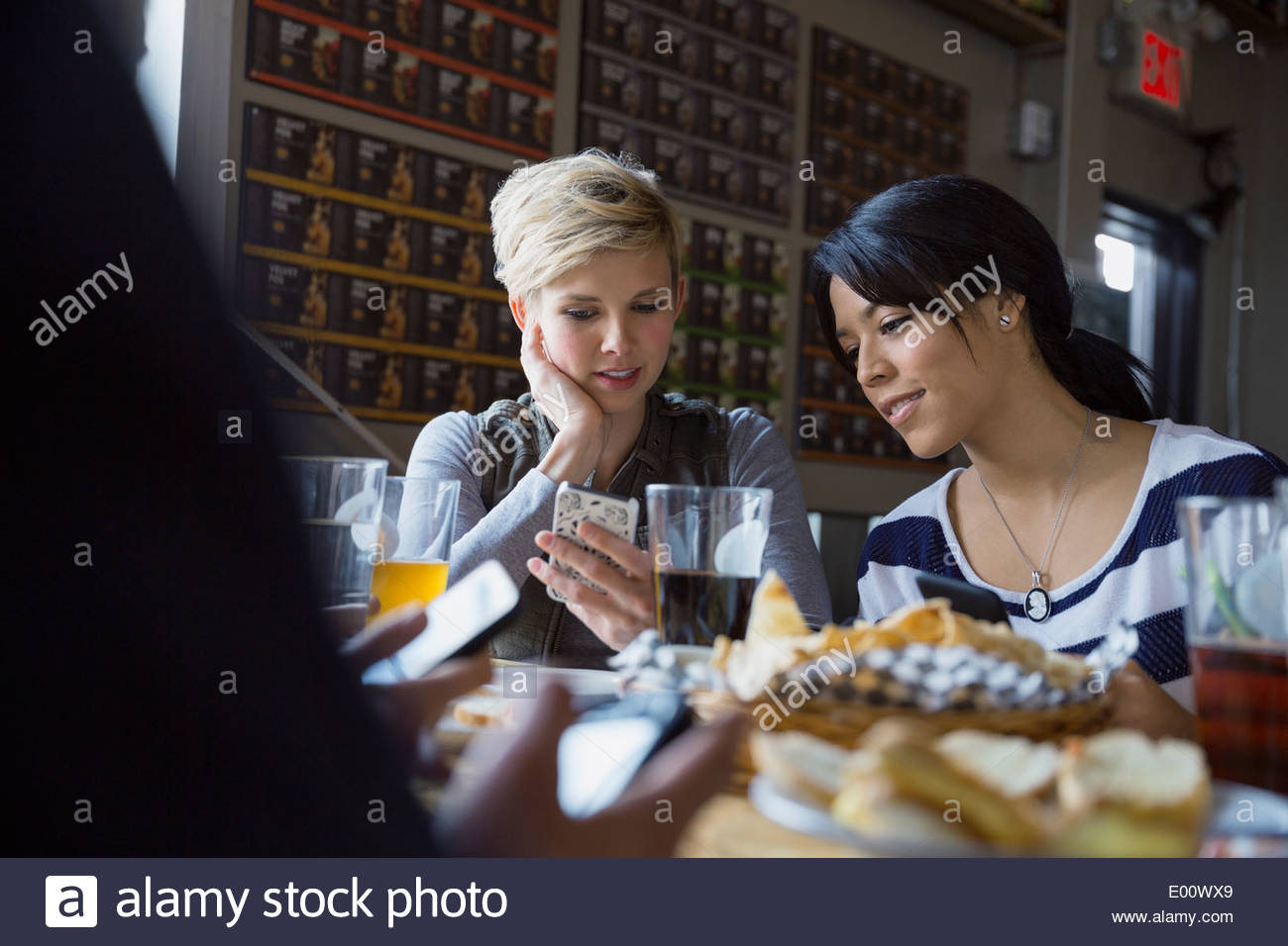 Friends text messaging with cell phones at brewery - Stock Image