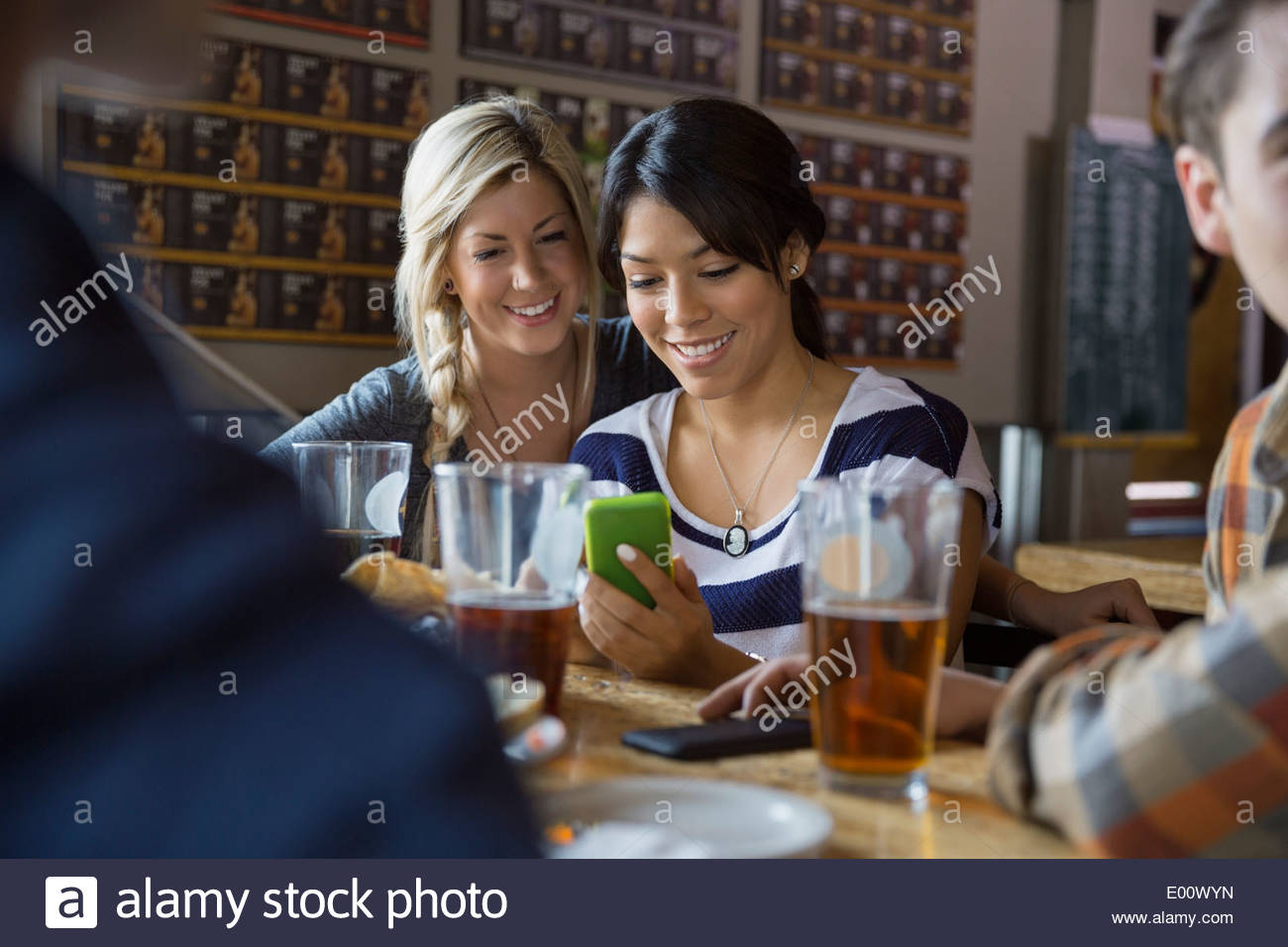 Friends text messaging with cell phone at brewery - Stock Image